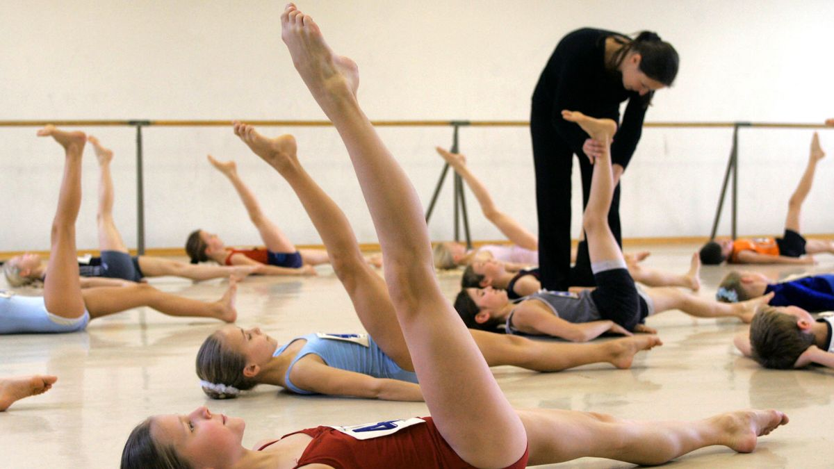 Künftige Ballettschüler dehnen ihre Muskulatur unter dem kritischen Blick der Tanzlehrerin.