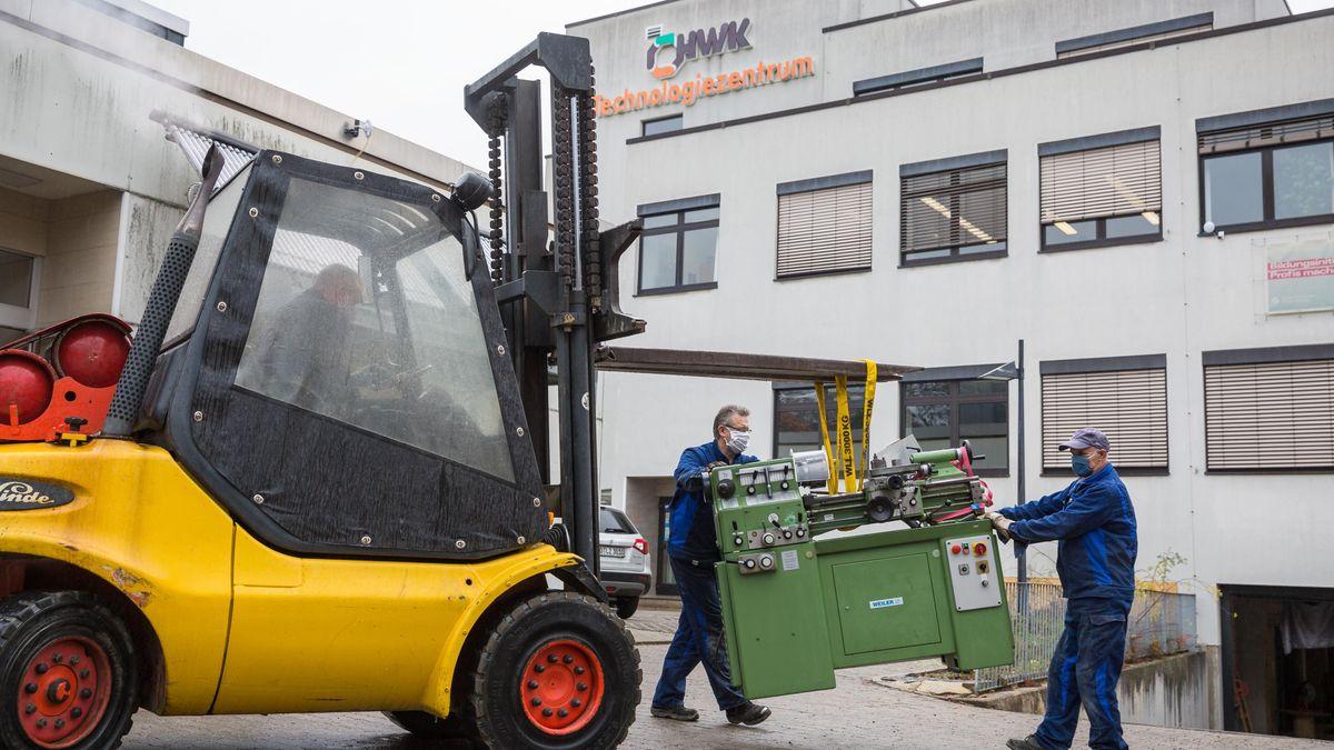 Zwei Männer in blauer Arbeitskleidung halten eine grüne Werkzeugmaschine im Gleichgewicht, die von einem Gabelstapler über den Hof gefahren wird.