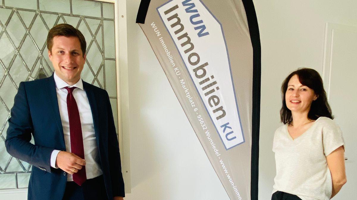 """Angela Schwarz in weißem Pullover und Bürgermeister Nicolas Lahovnik werden fotografiert, zwischen ihnen eine Fahne mit der Aufschrift """"WUN Immobilien KU""""."""