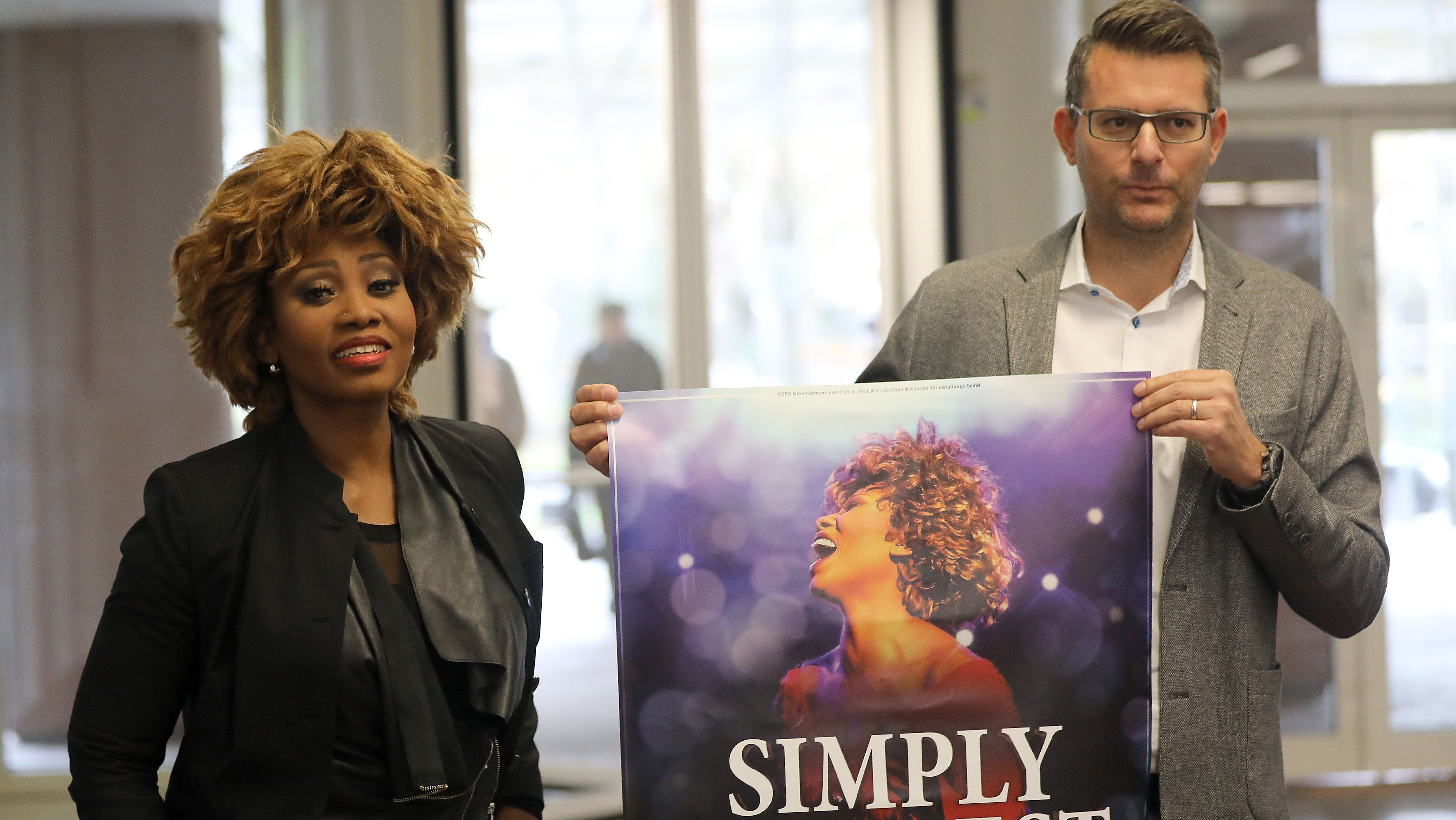 """""""Coco"""" Fletcher, Tina Turner-Darstellerin und Oliver Forster, Geschäftsführer der Konzertagentur Cofo Entertainment, mit Plakat im Gericht"""