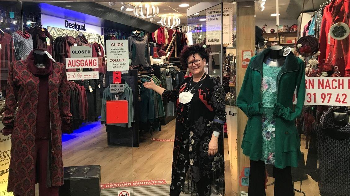 Frau in langem Kleid steht in einem Laden, in dem Damenkleidung an den Ständern hängt.