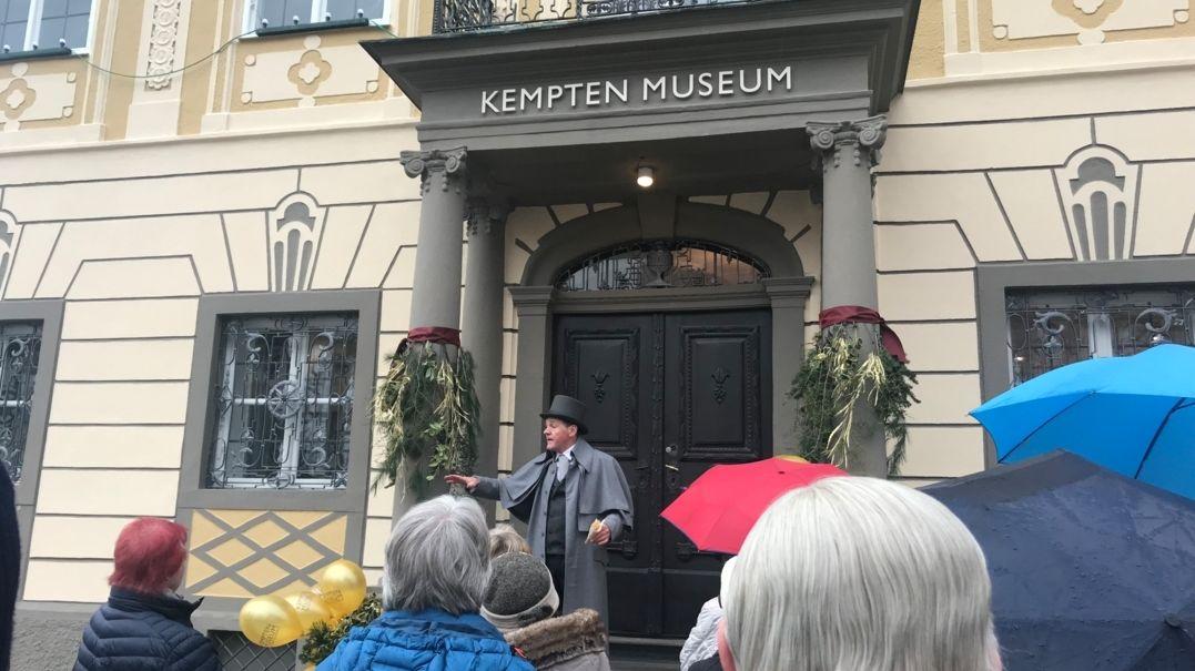 Vor einem Haus stehen Menschen und hören einem Museumsführer zu.