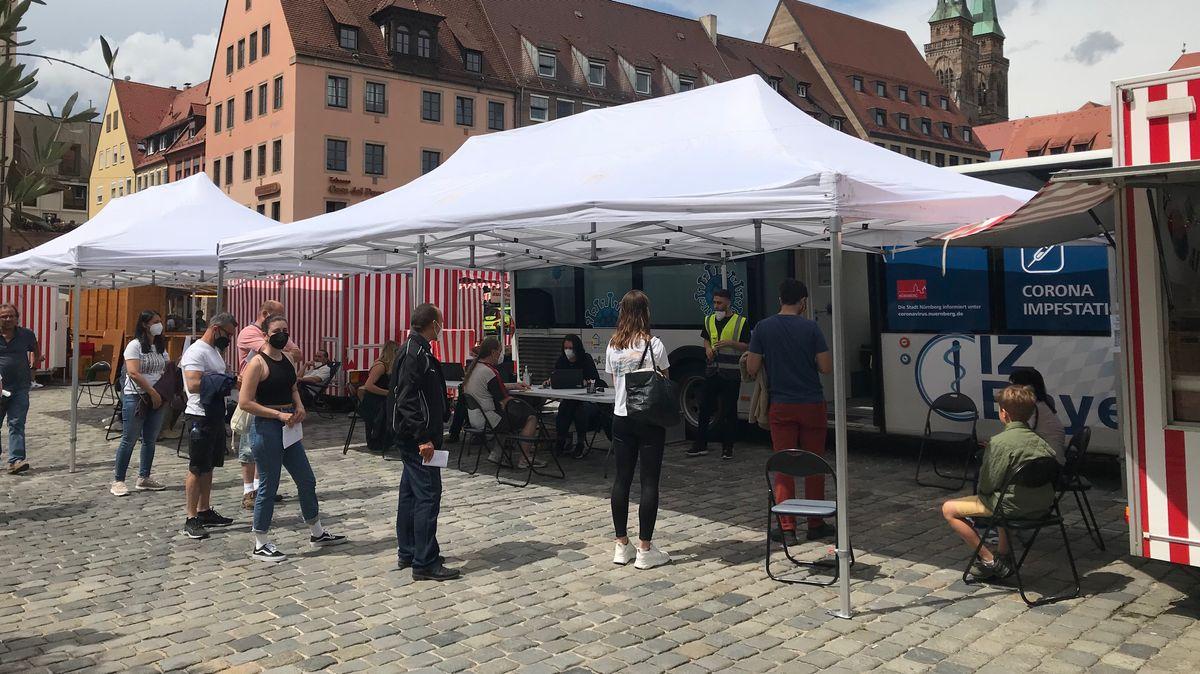 Mehrere Menschen stehen am Nürnberger Impfbus in der Schlange, um sich impfen zu lassen.