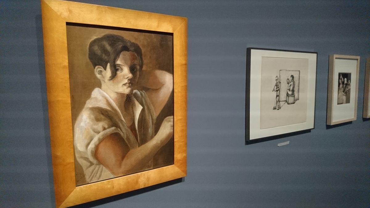 Vor grauer Wand hängen drei Bilder der Ausstellung. Zu erkennen ist links eine Frau mit hochgekrempelten Ärmel.