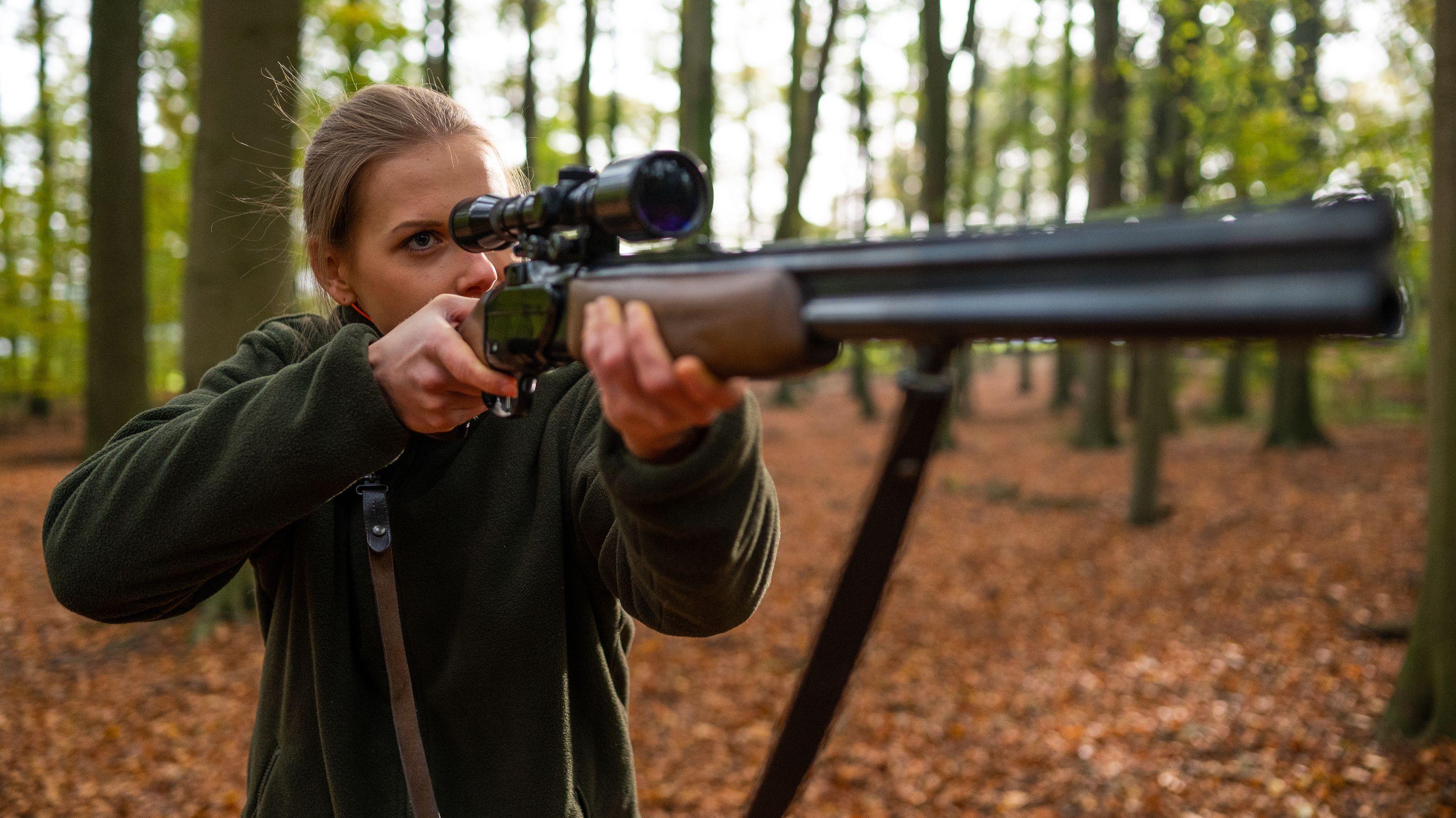 Die Jägerin Friederike Meyer steht mit ihrer Bockbüchsflinte im Wald