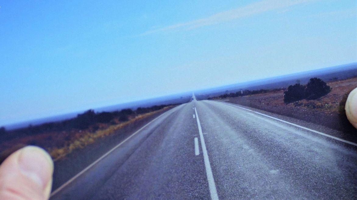 Nicolas Gkotses hält ein Erinnerungsfoto seiner Weltreise in der Hand, das eine lange, leere Straße zeigt.