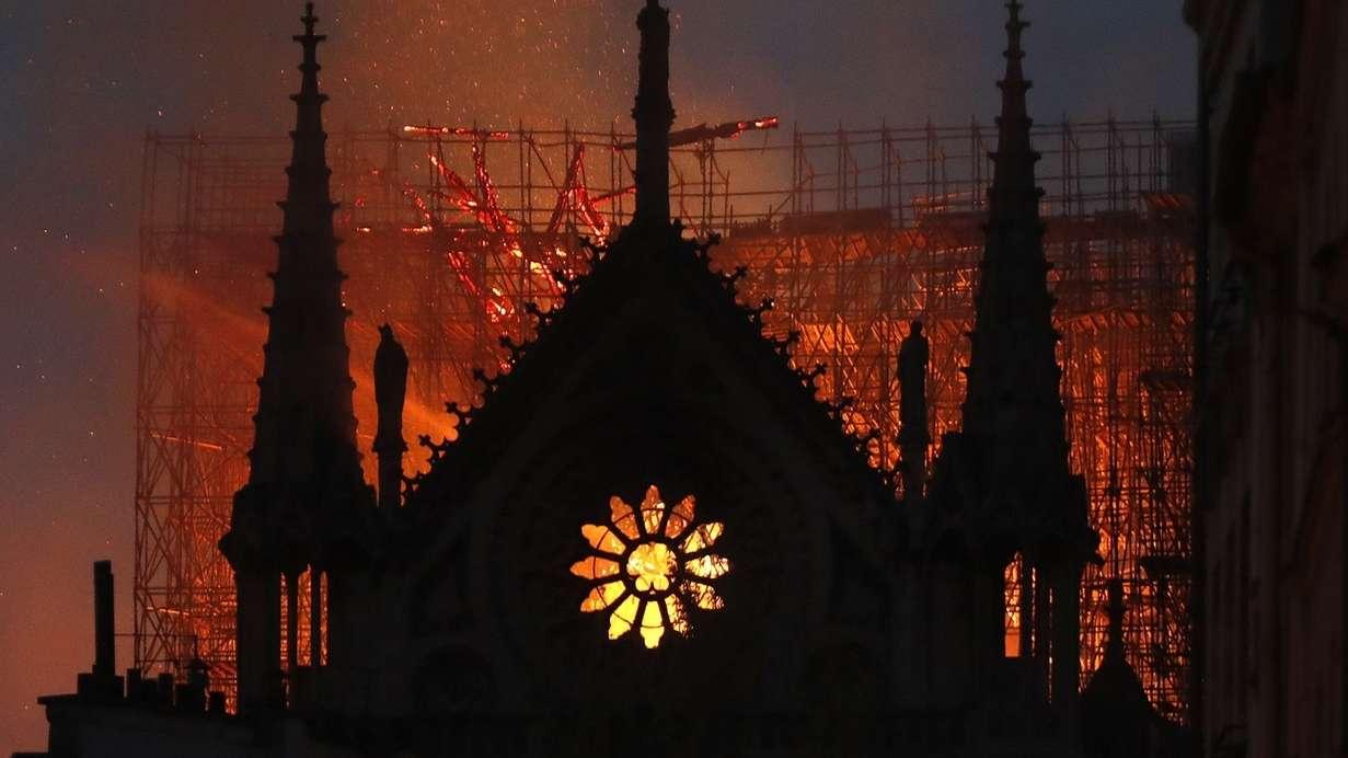 Während des Brands der Kathedrale Notre-Dame: Feuerschein hinter einem Fenster, Umriss der Fassade.