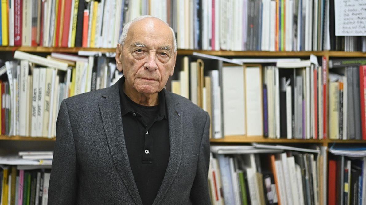 Ein Mann im Jackett steht vor seiner Bücherwand.