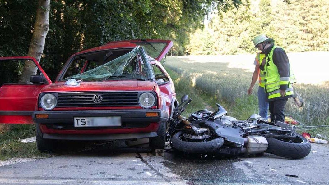 Auto und Motorrad nach dem Zusammenprall bei dem zwei Menschen starben. Einsatzkräfte stehen an der Unfallstelle.