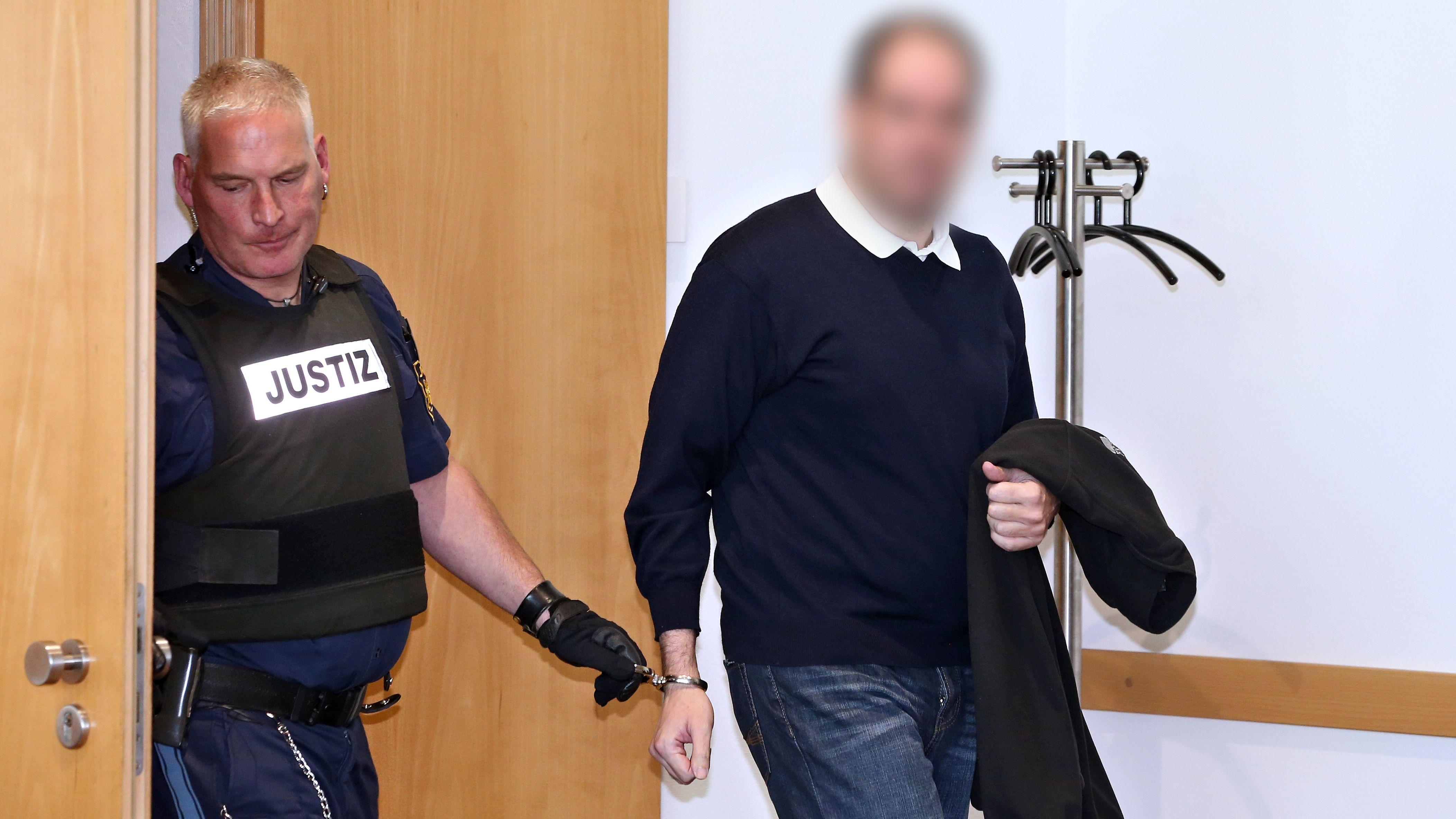 Der Kinderarzt, der wegen des Missbrauchs von rund 20 Jungen verurteilt wurde, wird in den Gerichtssaal geführt (Archivbild)