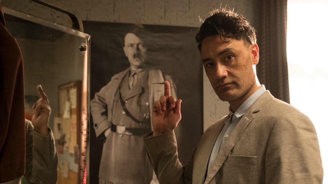 Regisseur Taika Waititi steht in der Drehkulisse und zeigt einem Poster mit Adolf Hitler den Mittelfinger