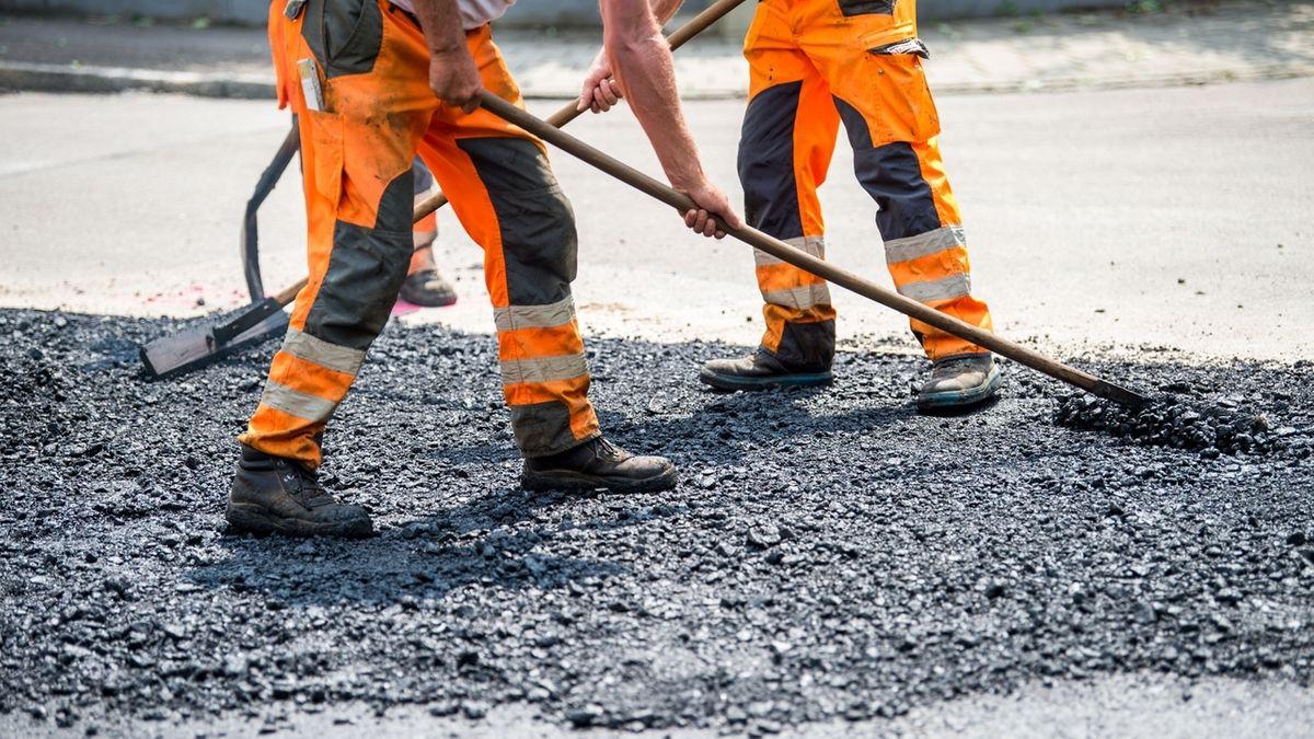 Bauarbeiter schieben auf einer Baustelle heißen Asphalt.