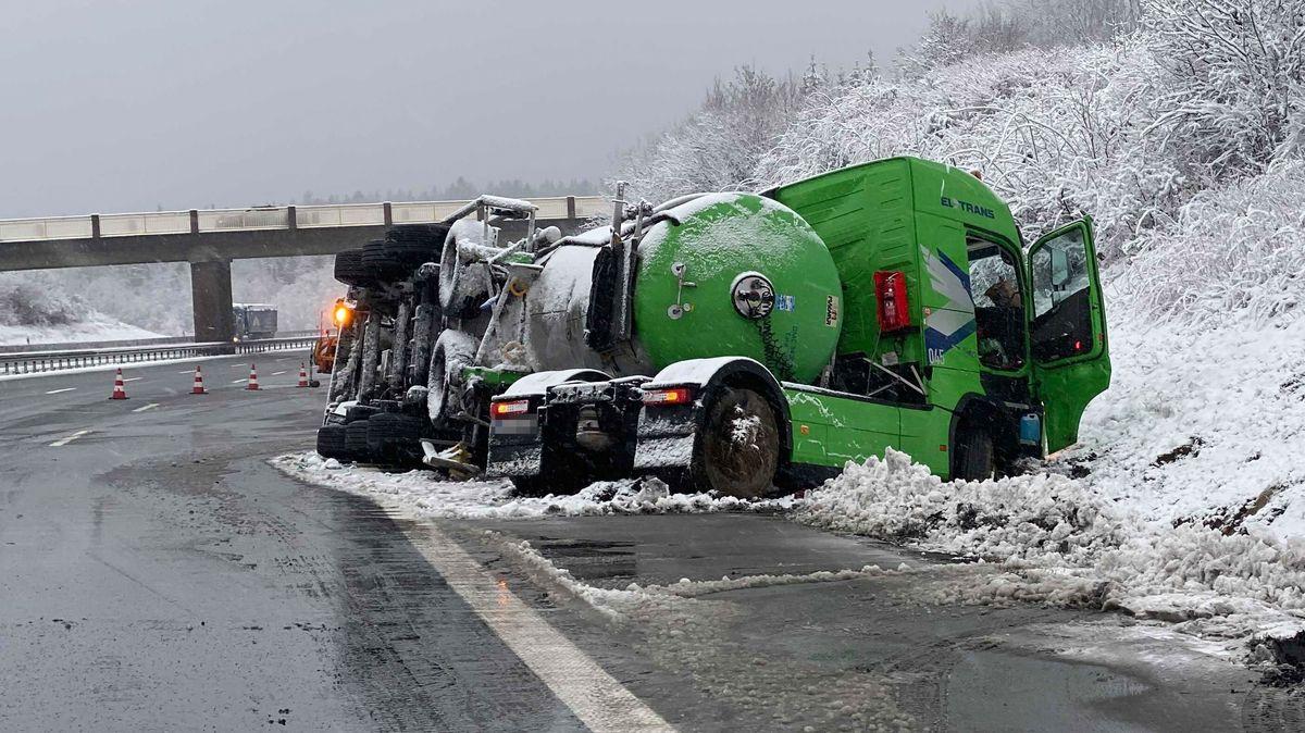 Eine grüne Sattelzugmaschine ist von der Fahrbahn gerutscht, der Tankanhänger ist umgekippt, dahinter die Autobahn.