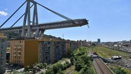 Trümmer der eingestürzten Brücke liegen auf Schienen, der stehen gebliebene Stumpf der Brücke ragt weit darüber in den Himmel.   Bild:dpa-Bildfunk/Luca Zennaro