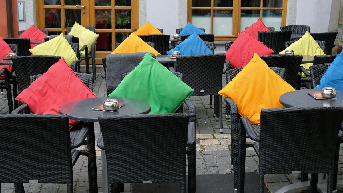 Der Außenbereich eines Cafés mit Stühlen und bunten Kissen.