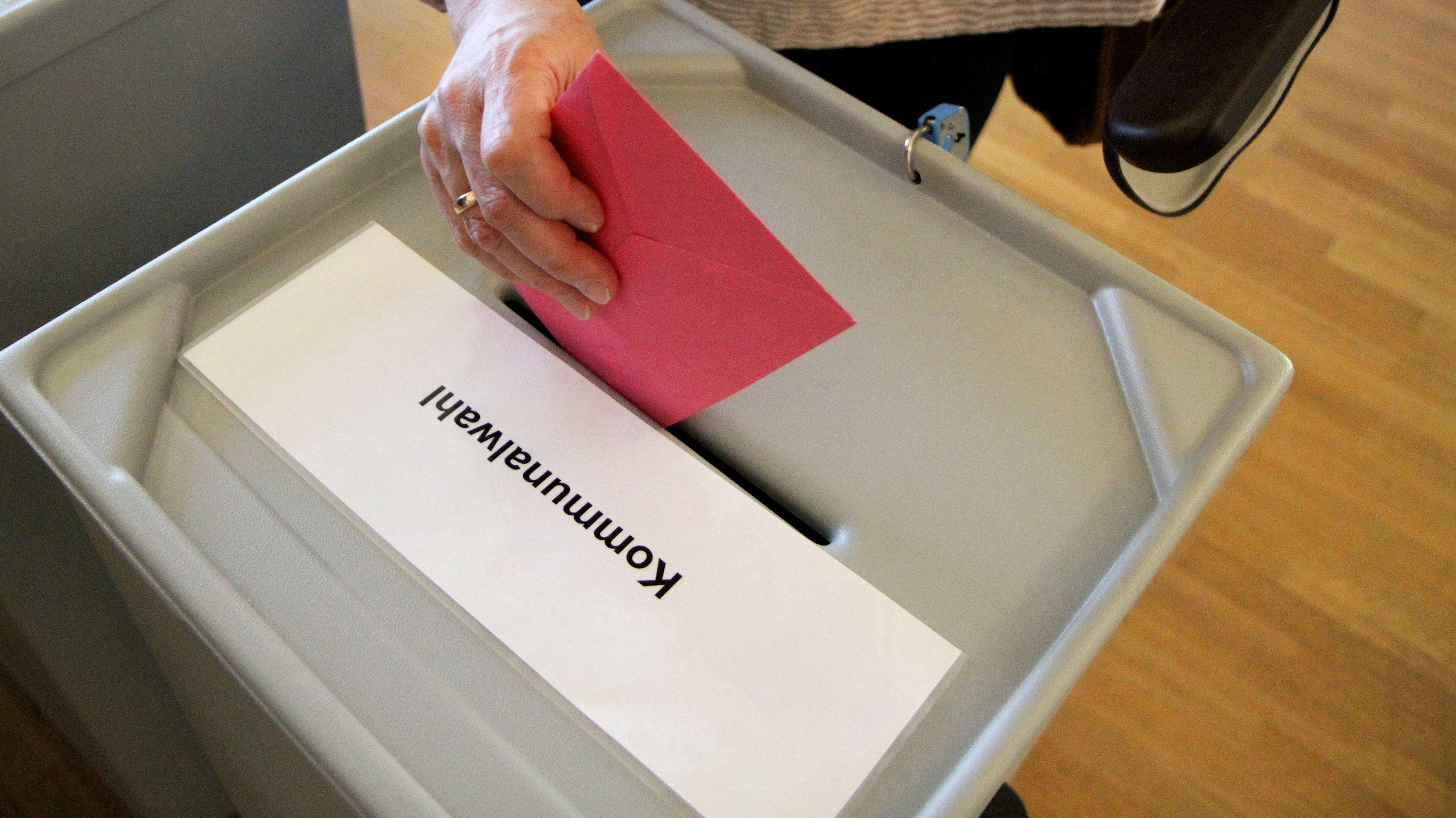 Wahlzettel wird in Wahlurne geworfen
