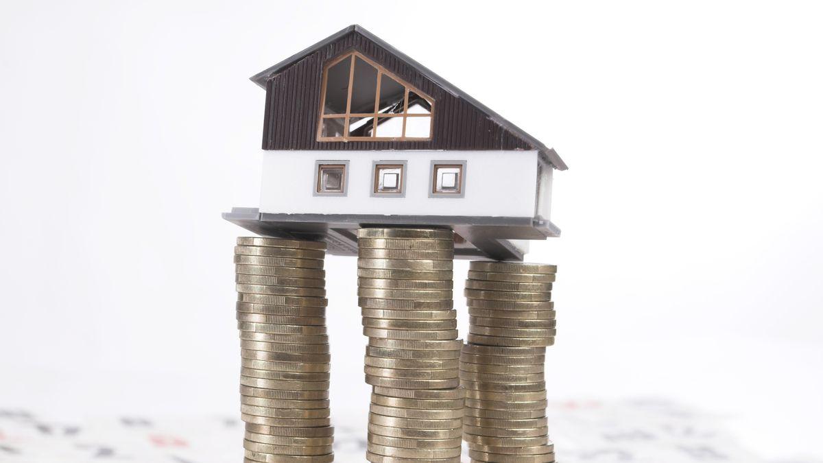 Eine Immobilie steht auf gestapelten Euromünzen (Symbolbild)