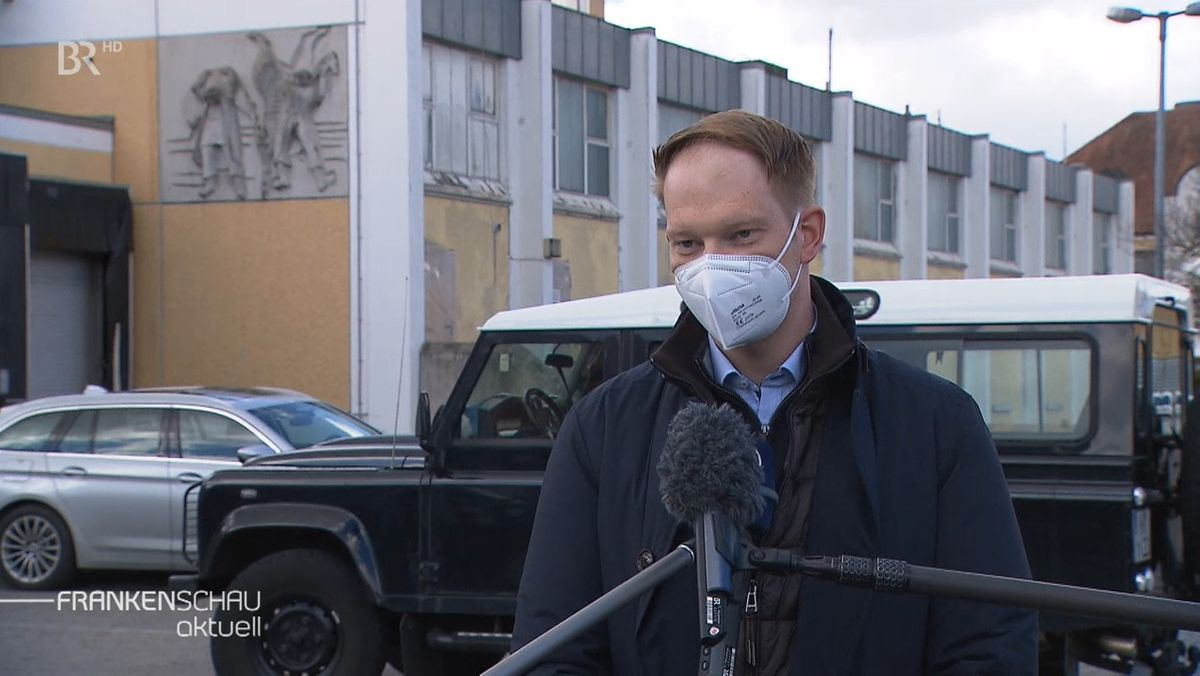 Ein Mann mit Mund-Nasen-Schutz steht vor einem Mikrophon und spricht.