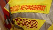 Das Logo des Arbeiter-Samariter-Bundes (ASB) auf einer gelben Jacke. | Bild:dpa/Jens Kalaene