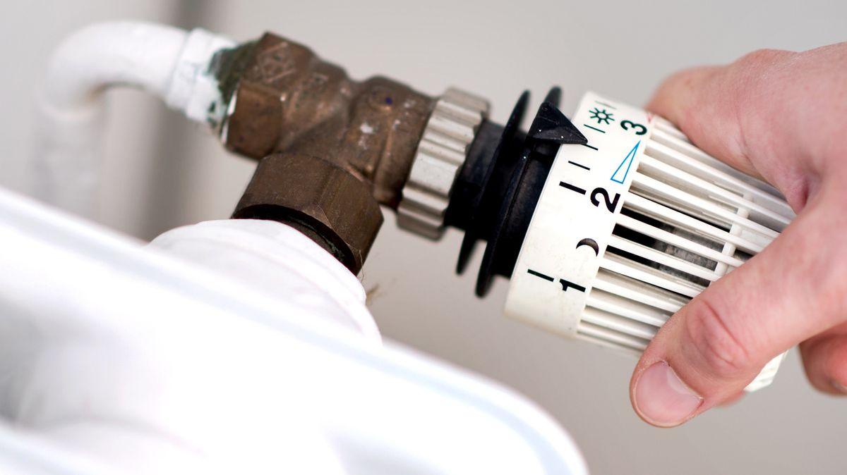 Eine Hand dreht am Thermostat einer Heizung (Symbolbild).