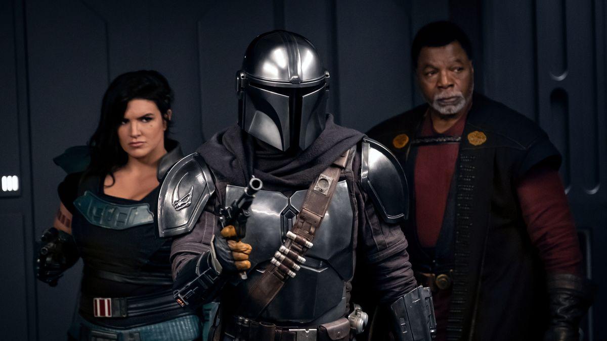 """Eine Mann und eine Frau, in der Mitte eine Gestalt in Ritterrüstung: """"The Mandalorian, Staffel 2"""" (Filmszene)."""