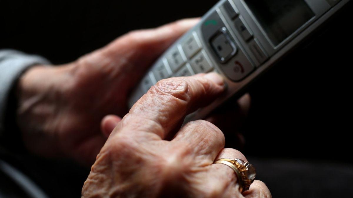 Person hält ein Festnetz-Telefon in der Hand.