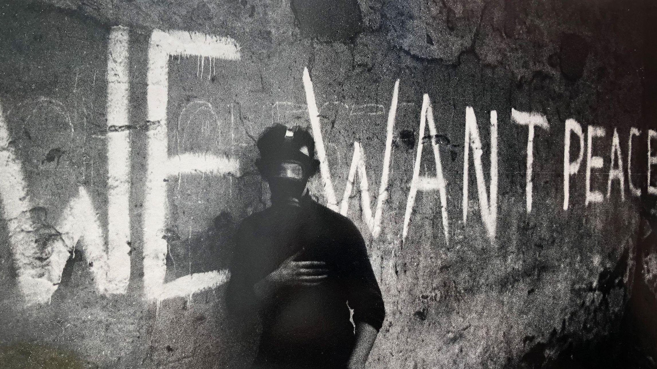 """Ein Mann steht mit einer Gasmaske vor einer Mauer, hinter ihm steht """"We want Peace"""" an der Wand."""