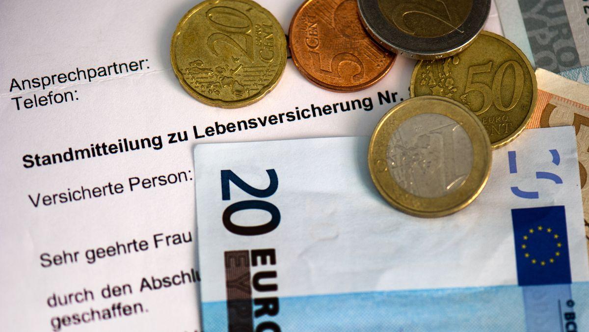 Neben einer Standmitteilung für eine Lebensversicherung liegen mehrere Euromünzen und Euroscheine.