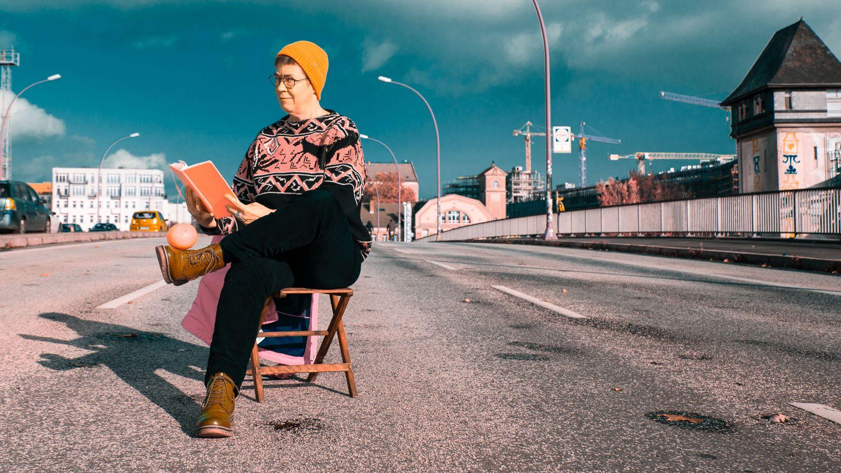 Die Philosophin Antke Engel, lesend auf einem Holzstuhl und auf einer Brücke mit Autoverkehr, bei sonnigem Wetteruer Himmel