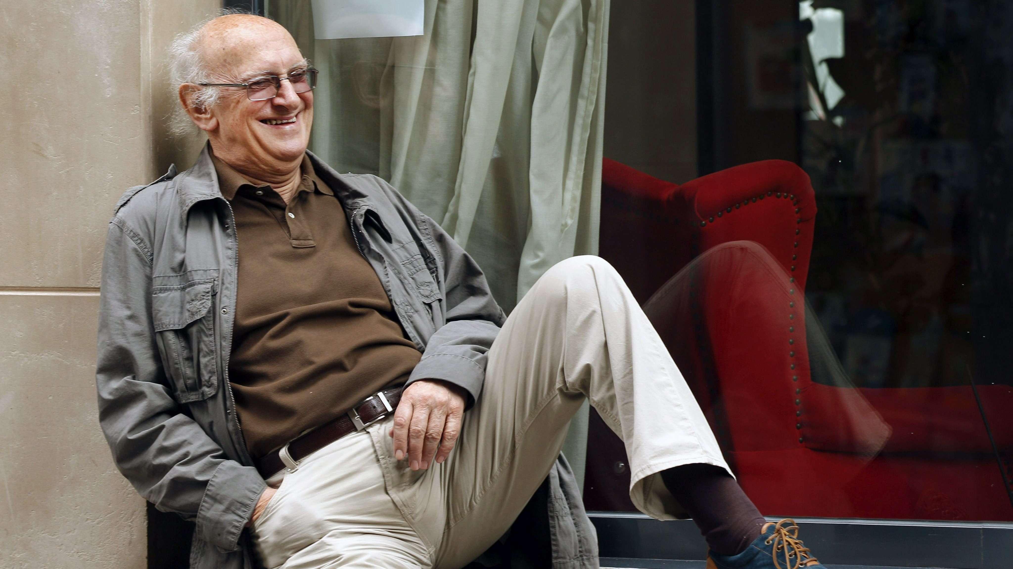Petros Markaris sitzt lässig auf einem Fensterbrett
