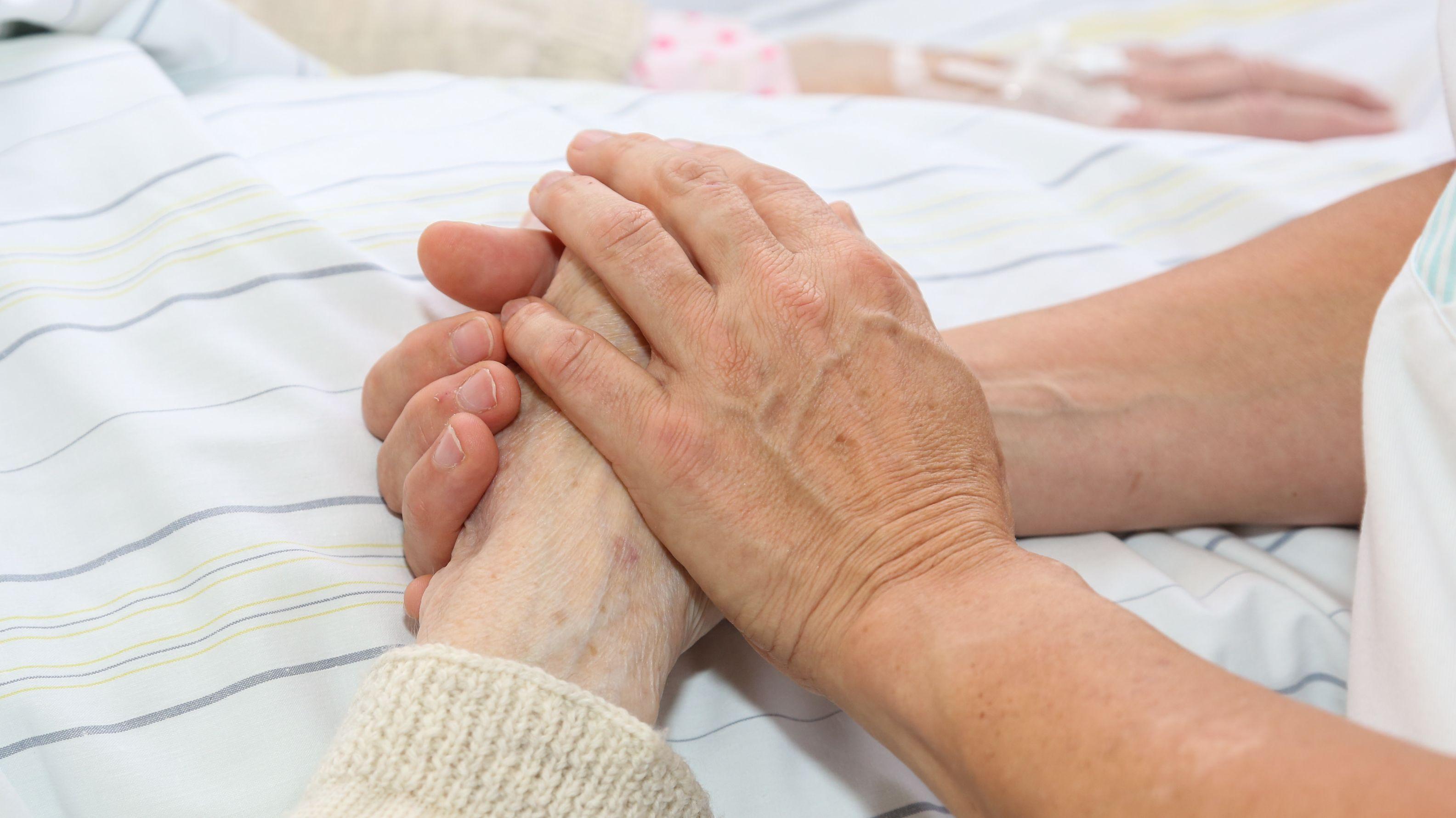 Eine Pflegekraft hält die Hand einer Patientin