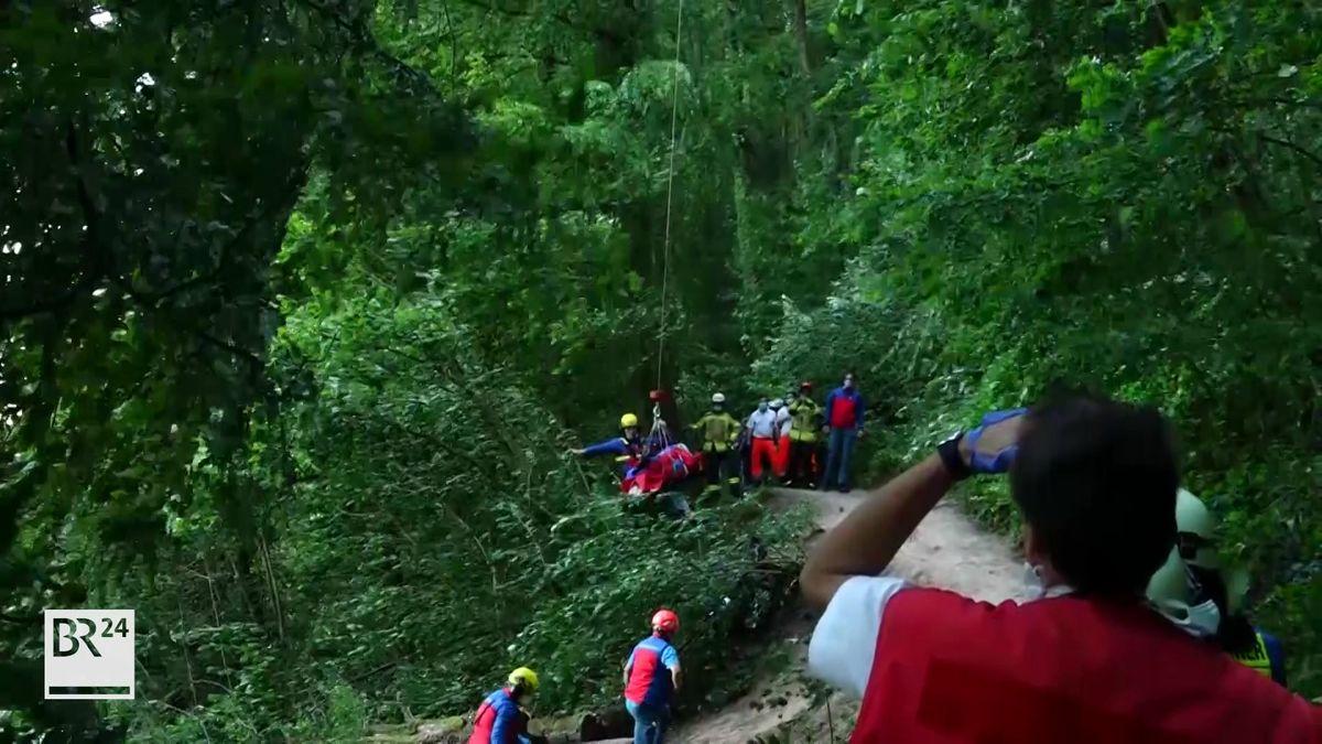 Rettungskräfte stehen an einem schmalen Weg in einem Wald.