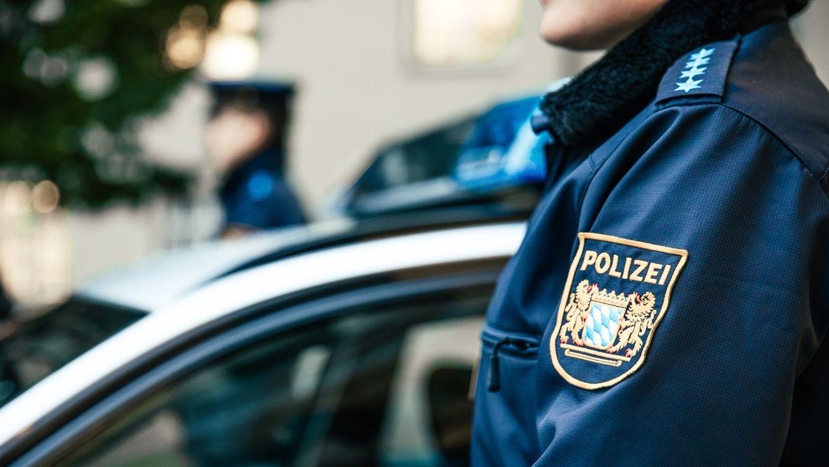 Bayerische Polizeibeamte in Uniform neben einem Einsatzwagen (Symbolbild)