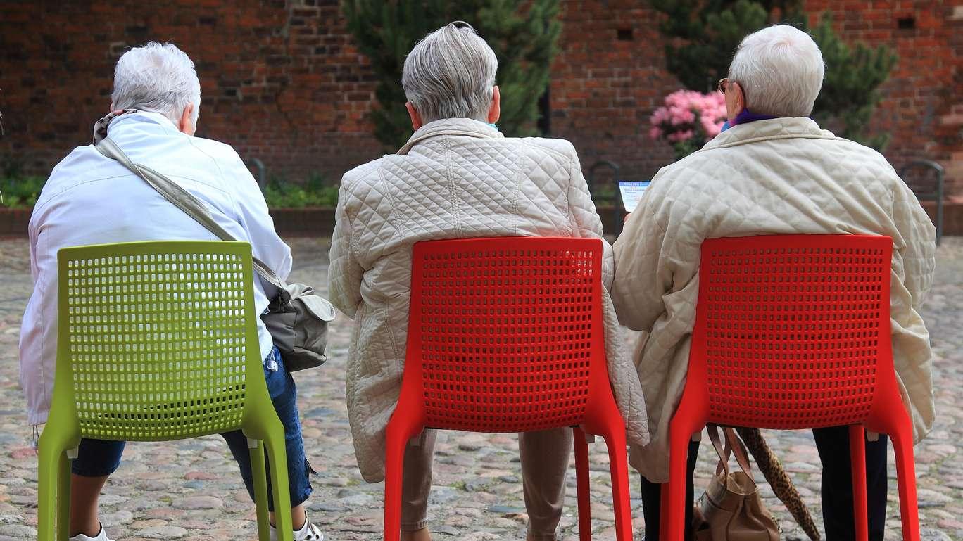 Seniorinnen sitzen auf bunten Stühlen