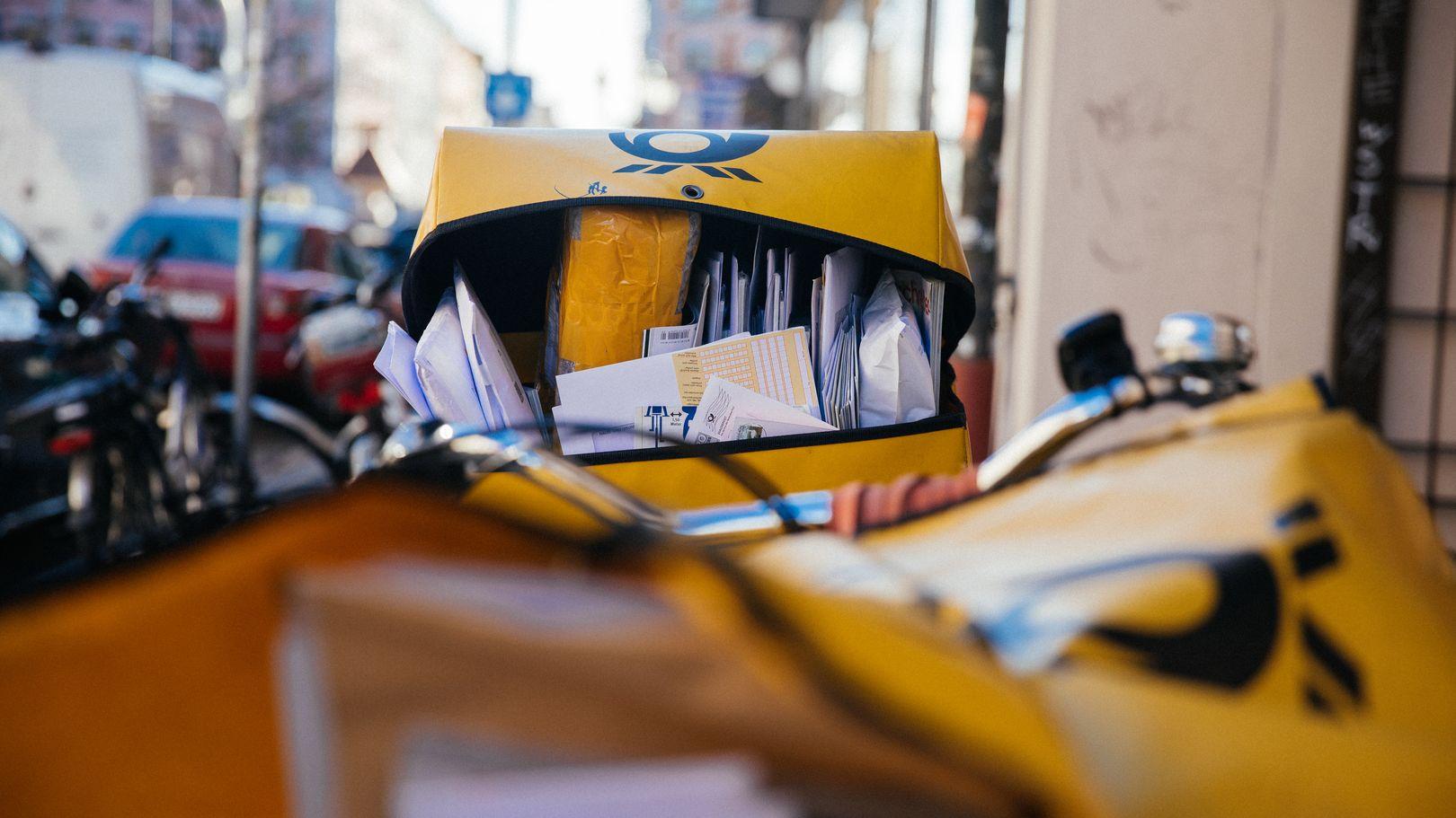Detailansicht zweier Postfahrräder, ein Briefkorb im Vordergrund, dahinter der Korb eines zweiten Rades.