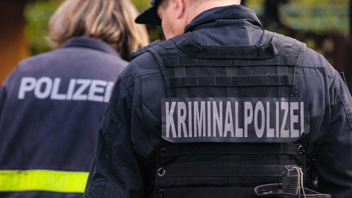 Zwei Polizeibeamte von hinten mit Aufschrift Kriminalpolizei und Polizei auf dem Rücken (Symbolbild)