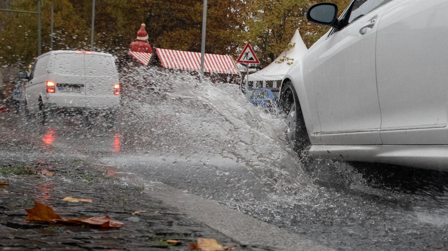 Ein Auto fährt durch eine Regenpfütze, so dass das Wasser auf den Bordstein spritzt