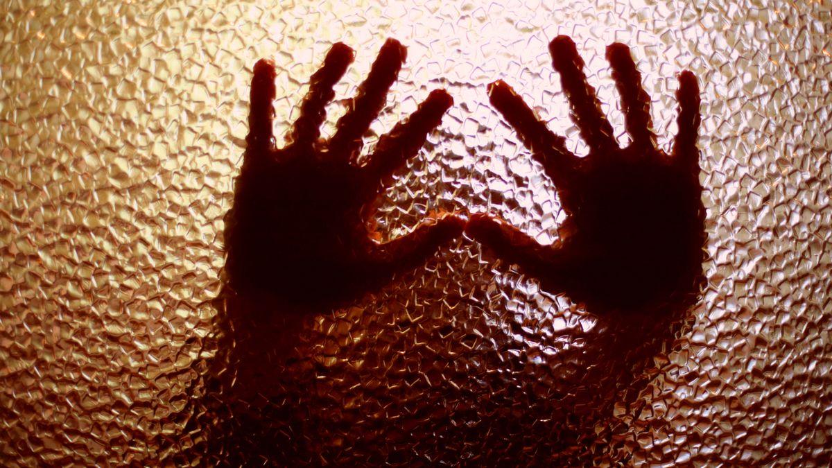 Symbolbild: Kind presst die Hände gegen eine Glasscheibe