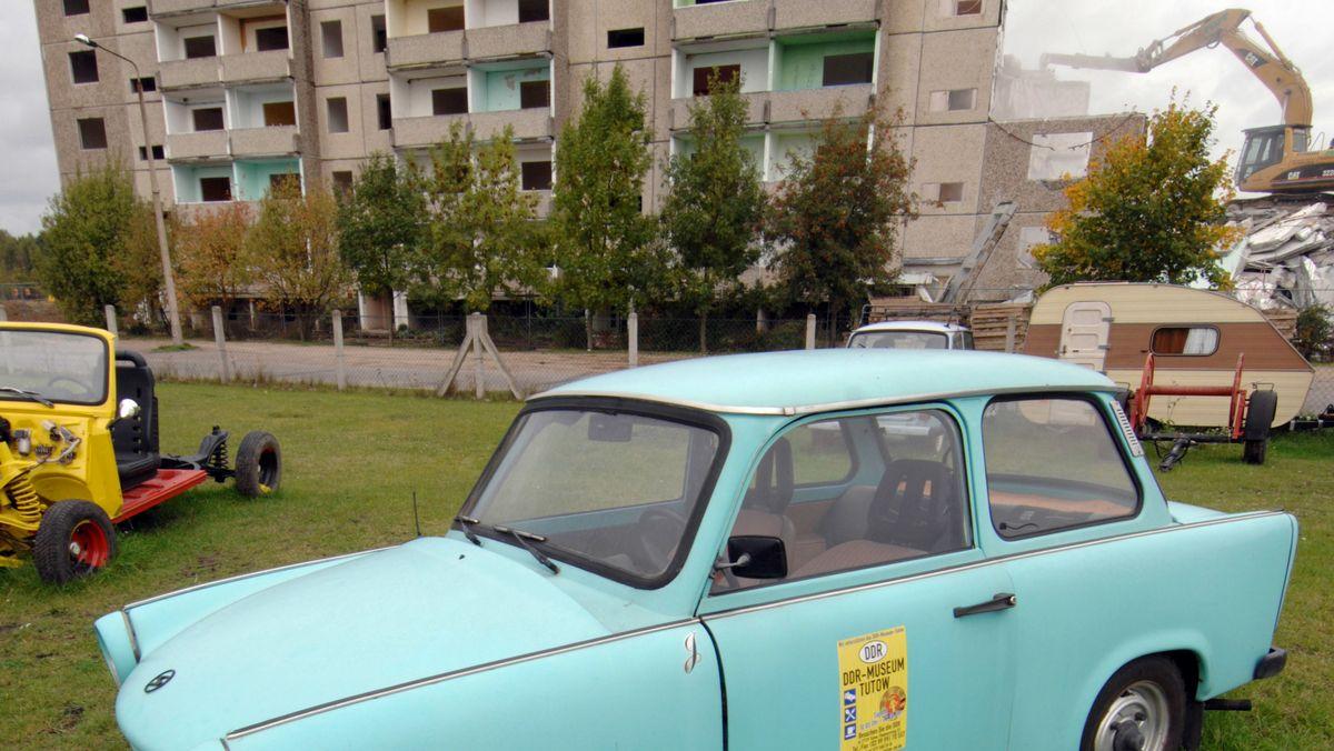 Im Hintergrund ein typischer Plattenbau, davor ist ein hellblauer Trabant geparkt.