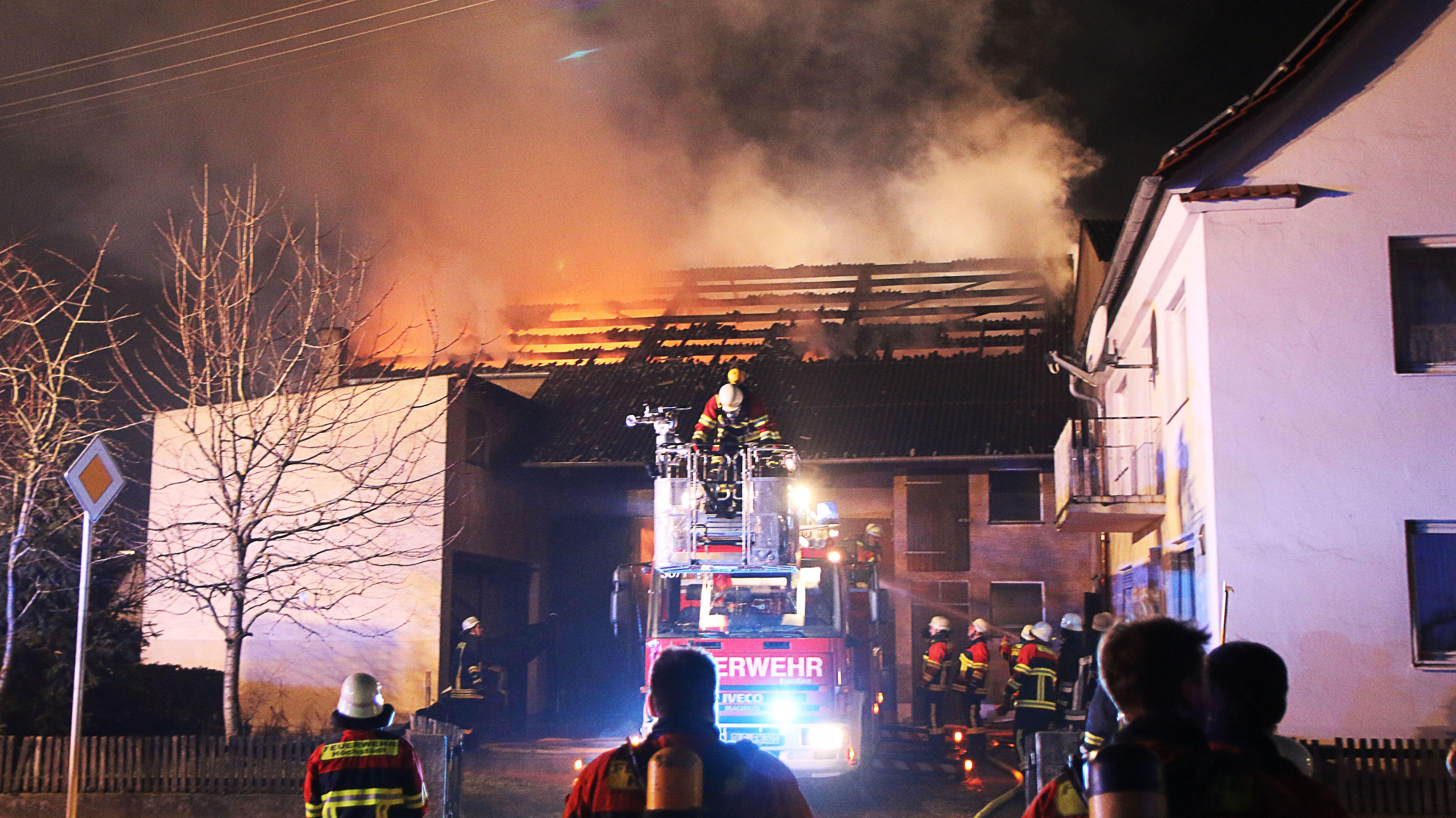 Einsatzkräfte der Feuerwehr mit Drehleiter bei einem Scheunenbrand in Deisenhofen