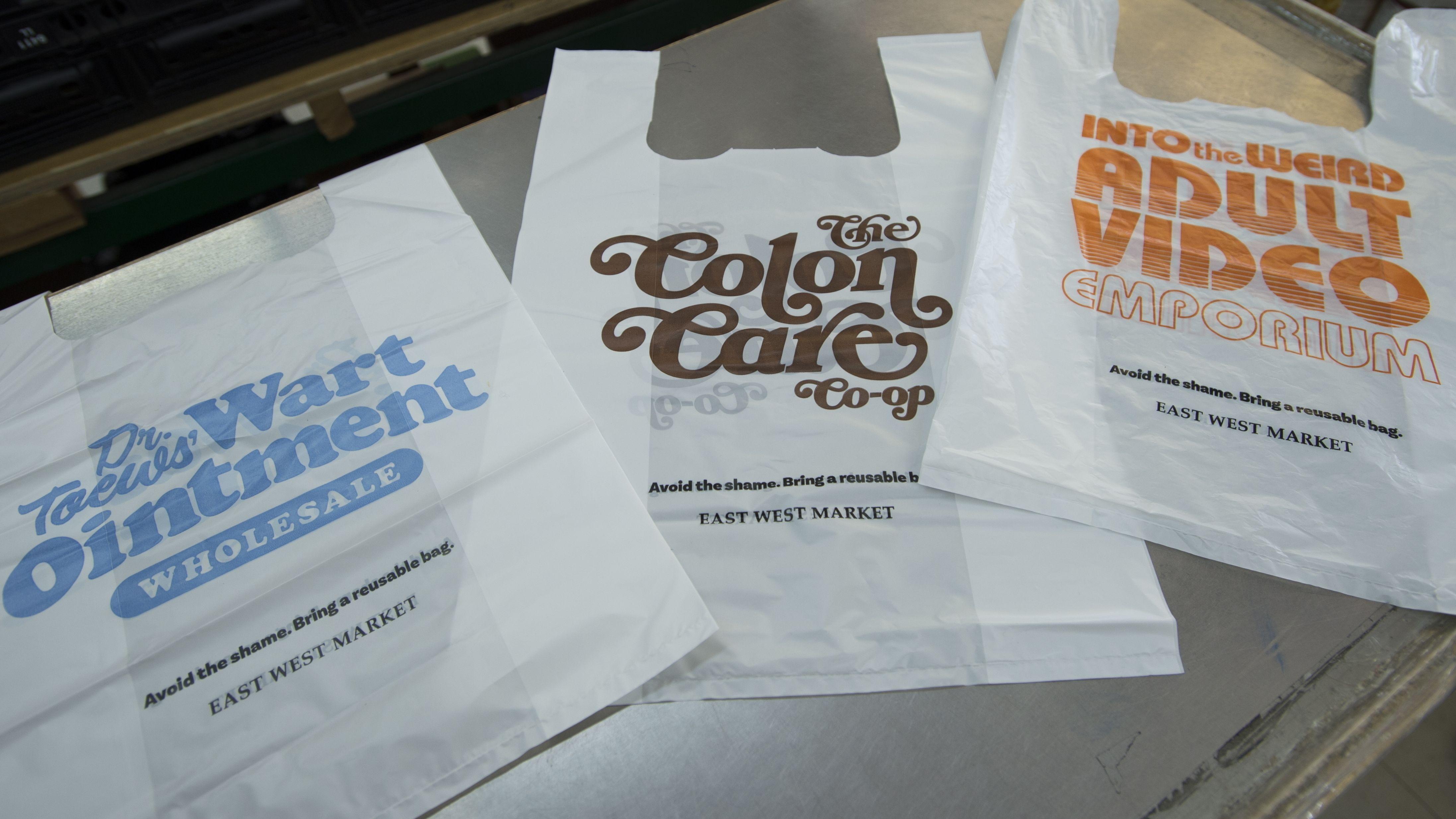 """Drei """"Plastiktüten der Schande"""" liegen an Supermarktkasse aus."""