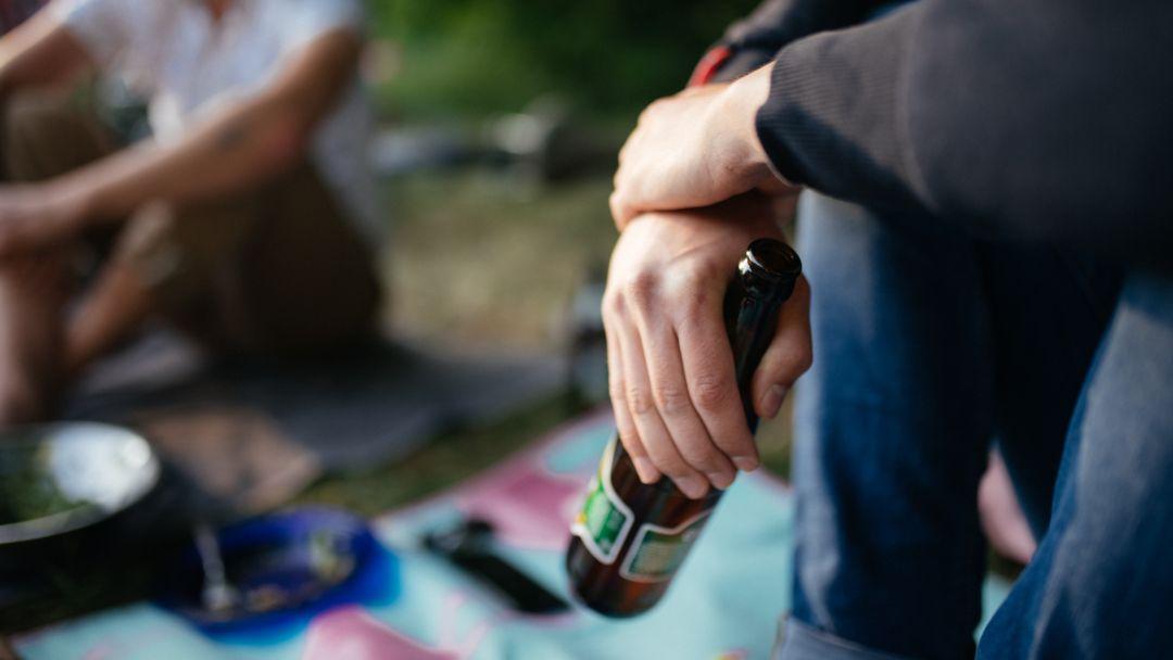 Ein junger Mann mit einer Bierflasche (Symbolbild)