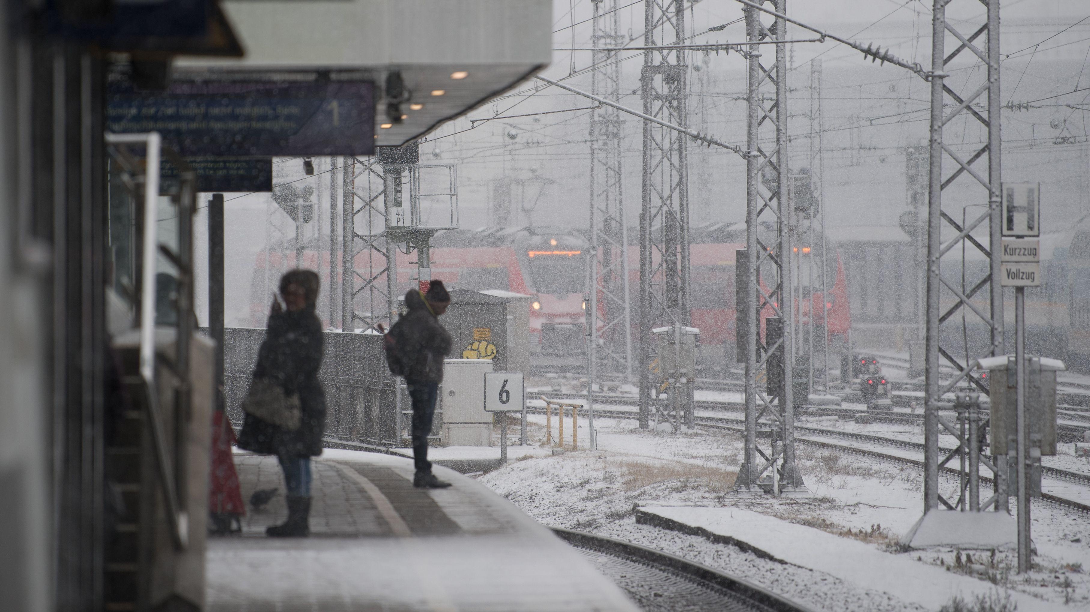 Fahrgäste warten bei Schnee auf einen Zug (Symbolbild)