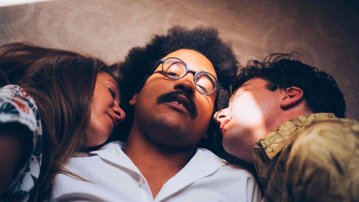 Die Gesichter der drei Musiker, die nebeneinander auf dem Boden liegen