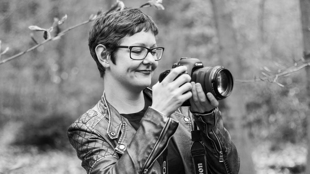 Filmemacherin und Fotografin Theresia Reinhold steht mit der Kamera unter Bäumen