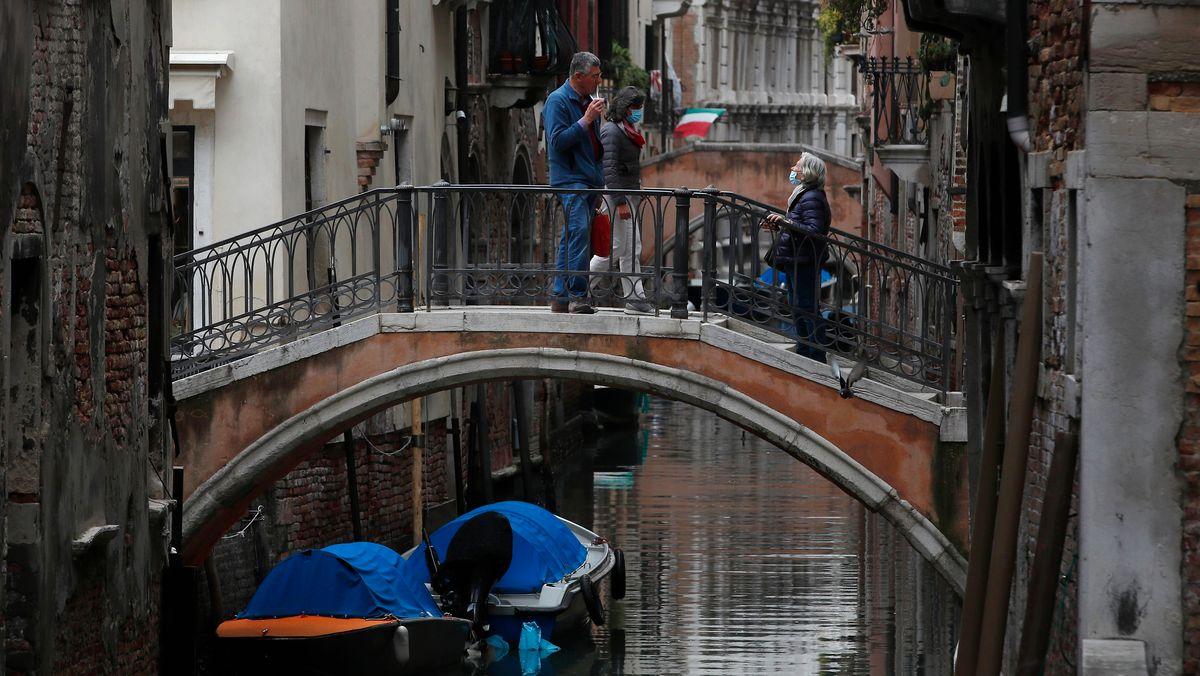 Venedig: Menschen unterhalten sich auf einer Brücke.