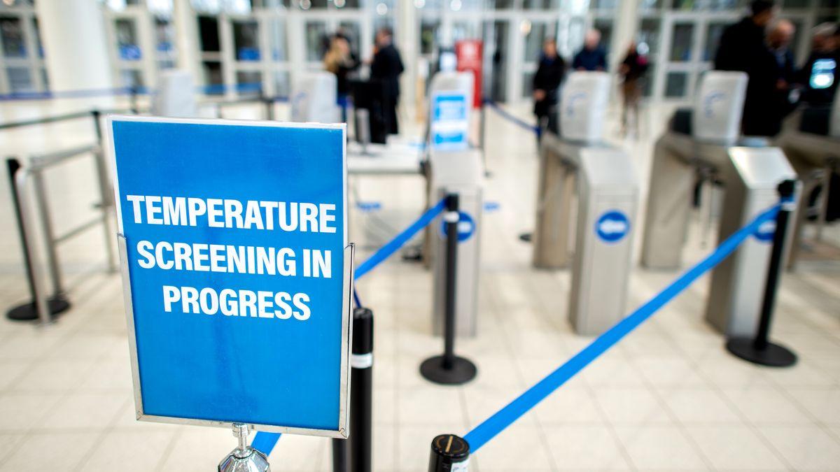 """""""Temperature Screening in Progress"""" weist am Eingang einer Einrichtung auf die Messung der Körpertemperatur hin"""