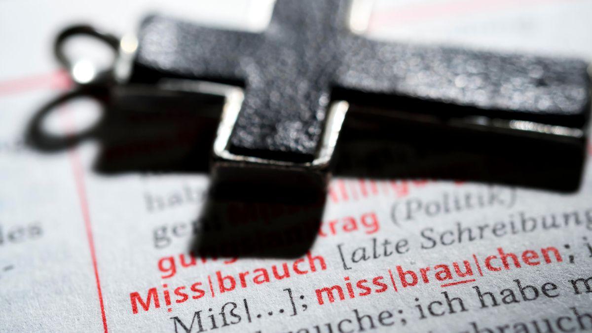 Ein Kreuz liegt auf einem Buch (Symbolbild)