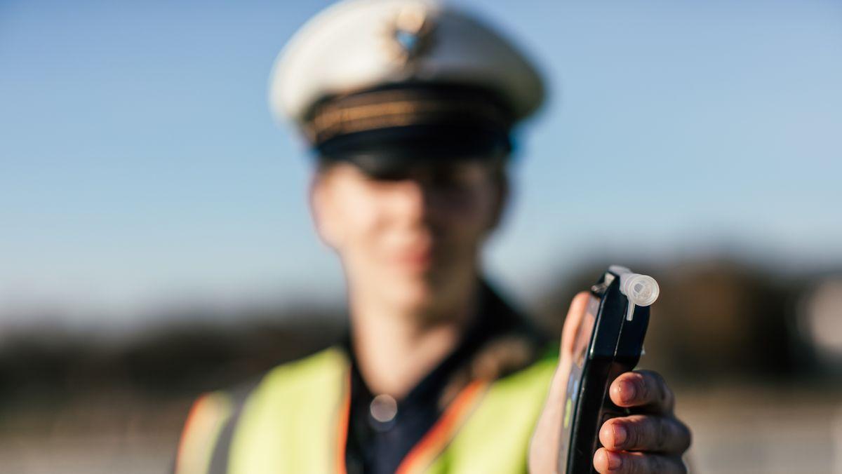 Eine Polizistin hält während einer Fahrzeug- und Personenkontrolle ein Alkoholmessgerät in der Hand.