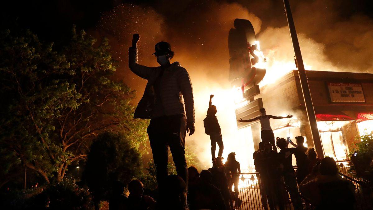 USA, Minneapolis: Demonstranten versammeln sich vor einem brennenden Gebäude eines Fastfood-Restaurants während der Proteste nach dem Tod von George Floyd